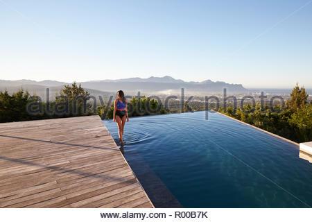 Boy bending over swimming pool - Stock Image