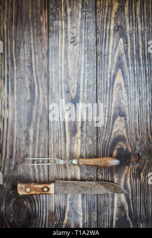 Vintage meat fork and butcher's knife over top a rustic wood table / background. Image shot from overhead view. - Stock Image