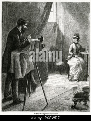 Photographer with bellows style camara taking a photograph of a posed victorian woman.     Date: 1878 - Stock Image