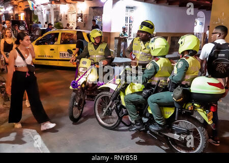 Cartagena Colombia Old Walled City Center centre Getsemani night nightlife Hispanic resident residents tourism police motorcycles public safety man wo - Stock Image
