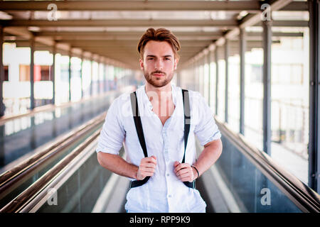 Handsome young man walking in city with backpack - Stock Image