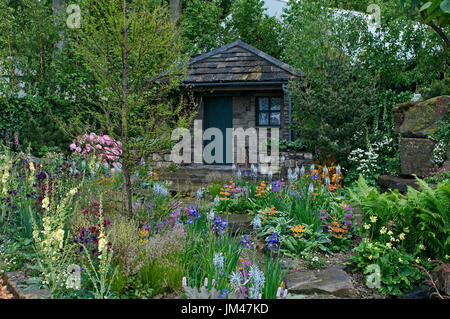 A country cottage and garden situated in a wooded rockery with a colourful display of flowers - Stock Image