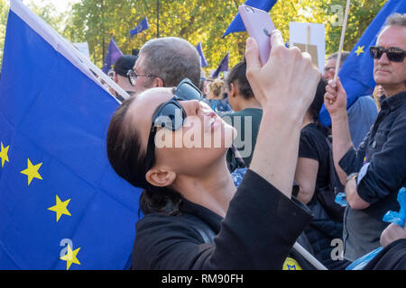 A young woman takes a selfie photograph in front of an EU flag during a march in London against Brexit - Stock Image