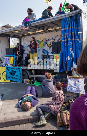 London, UK. 17th April 2019. People listen to a story-teller. Two days after Extinction Rebellion closed Waterloo Bridge turning it into a 'Garden Bridge' it remains closed to traffic despite a couple of hundred arrests. Activities continue on the bridge with new protesters arriving. Credit: Peter Marshall/Alamy Live News - Stock Image