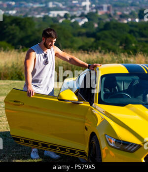 London, England. 25th June 2018. Two European, right hand drive Mustangs owned by father and son, Eugene Ring and Cameron Ring (in picture), in the sunshine of London's heatwave. It is said that this heatwave will continue into next week. Credit: Tim Ring/Alamy Live News - Stock Image