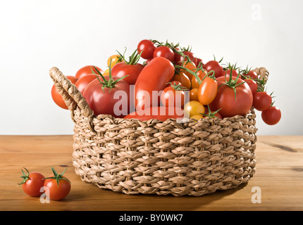 A basket with a variation of tomatoes - Stock Image