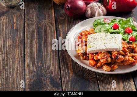 Baked giant beans with feta cheese and tomato sauce. Greek traditional food - Stock Image