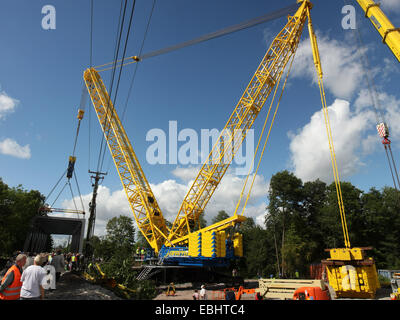 One of the biggest cranes in Europe, a Havator PC 6800, lifting a 300 ton railway bridge of steel on place over - Stock Image