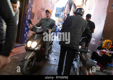 Busy Street scene Marrakech with motorbike and woman begging in the street, Marrakech Medina, Marrakesh, Morocco Africa - Stock Image