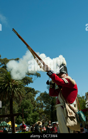 Adult man in period military costume, firing a muzzle-loading musket, face covered in smoke from cartridge ignition. - Stock Image