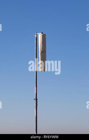 Limp, hanging wind sock in nil wind. - Stock Image