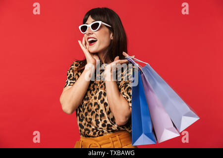 Image of a beautiful excited young woman dressed in animal printed shirt posing isolated over red background wearing sunglasses holding shopping bags. - Stock Image