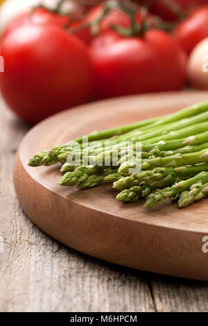 fresh asparagus on a cutting board and tomatoes on a wooden background close-up - Stock Image