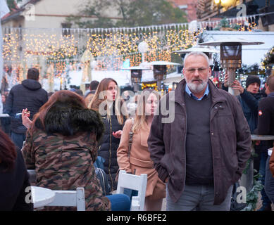 Gray hair and beard Man smoking cigar walking in crowd at the Christmas Market in Zagreb's main Square. Annual event currently on-going - Stock Image
