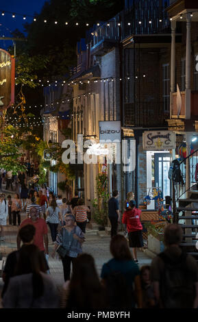 Tourists walking during a summer evening on Rue du Petit-Champlain in old Québec City, Canada.  Rue du Petit-Champlain lined with shops and restaurant - Stock Image