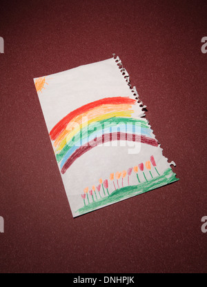 A children's colored pencil drawing of a rainbow and flowers. - Stock Image