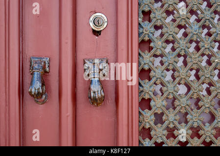 Detail of a red door featuring door knockers in the shape of the Hand of Fatima, in the village of Estoi, Algarve, - Stock Image