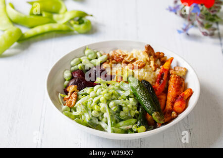 Buddha bowl with roast beetroots, carrots, zucchini and green peas salad - Stock Image