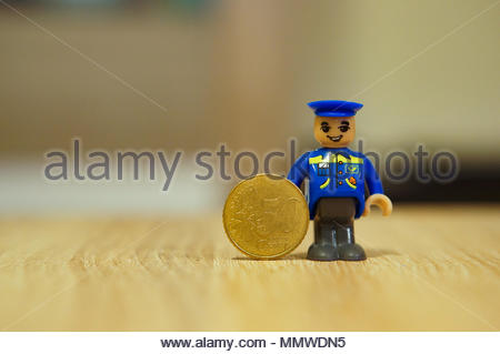 Plastic toy postman standing next to.a 50 eurocent coin - Stock Image