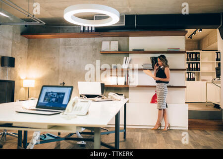 Businesswoman holding file and talking on smart phone in office - Stock Image
