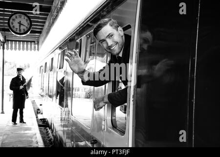 Vintage train arrives at railway station with handsome air force officer in uniform leaning out of window, laughing and waving - Stock Image