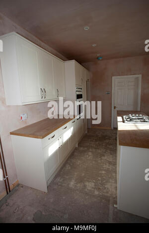Newly fitted kitchen with freshly plastered walls - Stock Image
