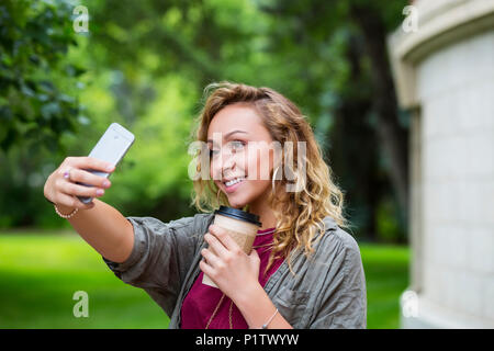 A beautiful female university student taking a self-portrait with her smart phone on the campus; Edmonton, Alberta, Canada - Stock Image