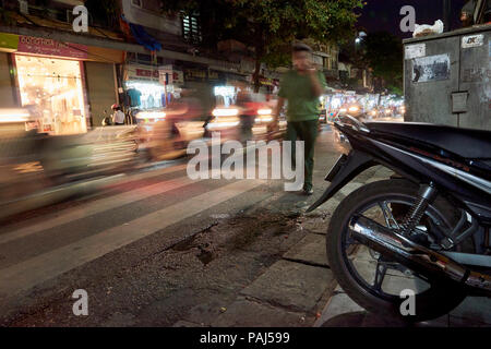 A motion blurred man walks next to busy traffic at night at the streets of Hanoi's Old Quarter, Vietnam, framed by a parked motorbike in the foregroun - Stock Image