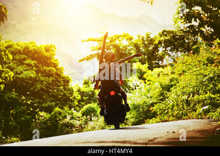 Happy couple tripping by motorcycle on tropical road at sunset time - Stock Image