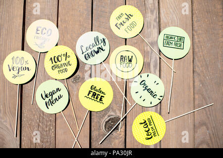 Green stickers with healthy food slogans on the wooden table - Stock Image