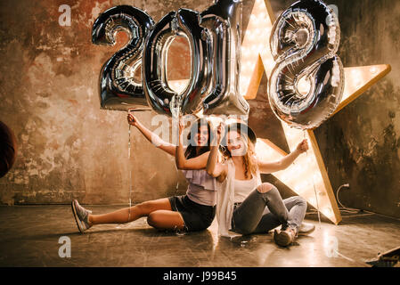 Two young girlfriend celebrates the 2018 with big ballons who forms 2018 on a cinema retro background - Stock Image