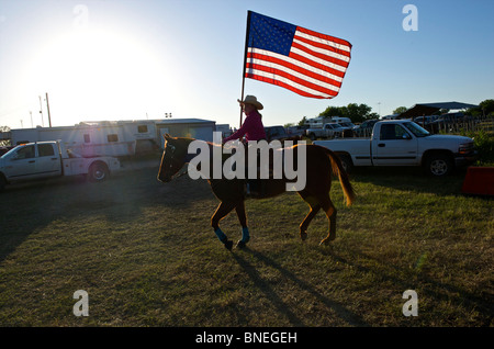 Cowgirl waving American flag at opening ceremony of PRCA rodeo event in Texas, USA - Stock Image