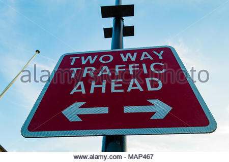 Two way traffic ahead sign, white reflective lettering on a red background, Southport, Merseyside England UK - Stock Image