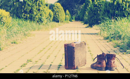 Old shabby leather ankle boots, next to an antique suitcase, in the middle of a yellow brick road. Sixteen-by-Nine crop. Nashville effect added. - Stock Image
