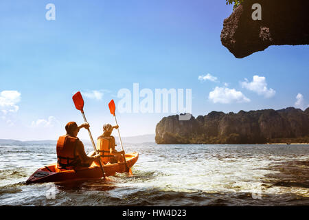 Couple canoeing at sea island backdrop - Stock Image