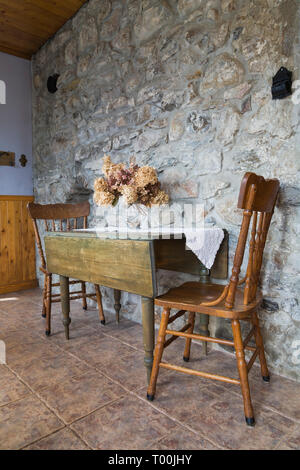 Antique wooden dining table and chairs in entryway with fieldstone wall and terracotta ceramic tile floor inside an1820 cottage style fieldstone home - Stock Image