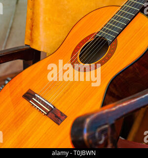 Classic guitar musical instrument lays in an armchair. Closeup view. Square photo - Stock Image