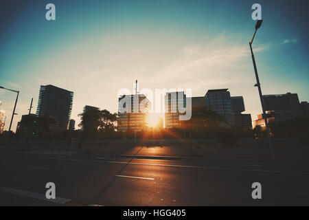 Wide angle shot of dramatic sunset with flare and godrays in residential district of Barcelona with houses in distance - Stock Image