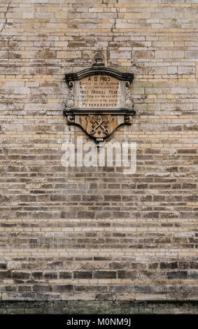 Detail of Jurassic limestone wall of building in Cumbergate, central Peterborough, with self-explanatory plaque - Stock Image