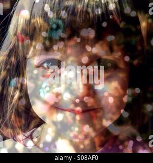 Multiple exposure toddler girl and Christmas lights. - Stock Image