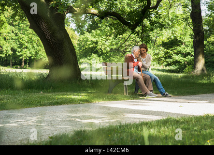 Senior woman sitting on park bench with granddaughter - Stock Image