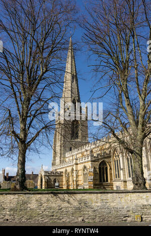The spire of St Mary's church, framed by the branches of winter trees, Higham Ferrers, Northamptonshire, UK - Stock Image