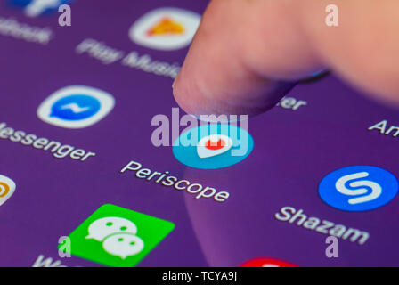 Finger pressing the Periscope app icon on a tablet or smartphone touchscreen. - Stock Image