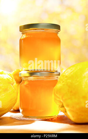 Quince jelly in glass jars with quinces on a wooden table in bright sunshine in front of an yellow and orange background. - Stock Image