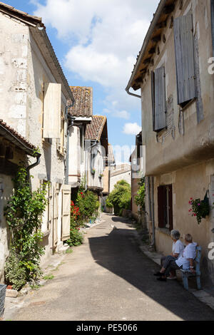 Two senior women sitting in a medieval street, Issigeac bastide town, Dordogne France Europe - Stock Image