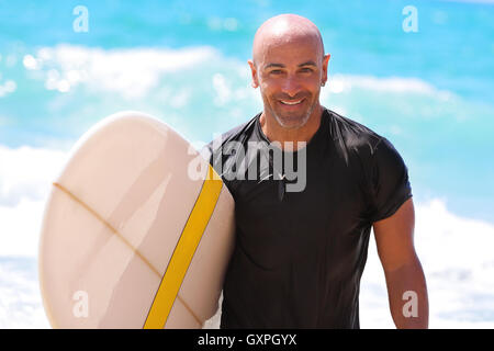 Portrait of a handsome man with surf board in hand, beautiful surf trainer on the beach, enjoying water sport, active - Stock Image