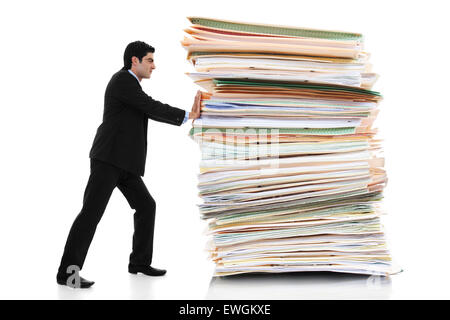 Stock image of businessman pushing a giant stack of documents isolated on white background - Stock Image