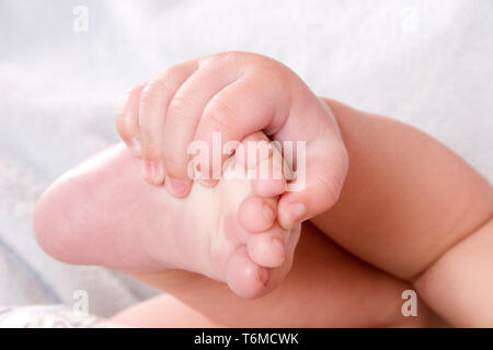 close up of baby's hand grasping his foot - Stock Image