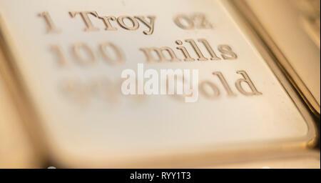 Gold bullion 999.9 purity solid one ounce ingot precious metal bars. - Stock Image