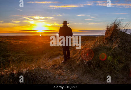 Southport, Merseyside. 20th March 2019. UK Weather. Colourful sunset over the Irish Sea and Ainsdale Sand Dunes National Nature Reserve (NNR), which is a coastal site comprising rare dunes, beach and woodland habitats. Credit: MediaWorldImages/Alamy Live News - Stock Image
